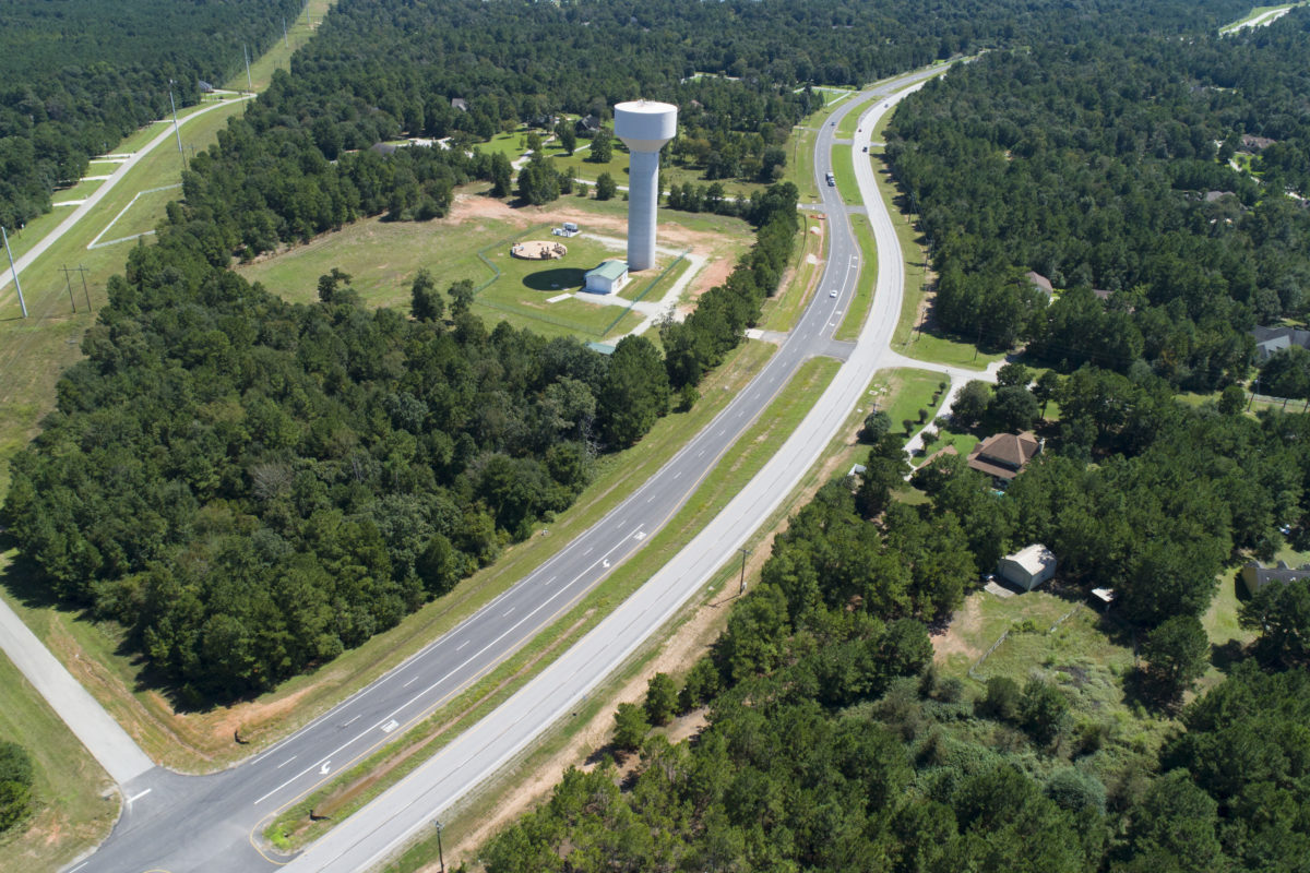 Aerial image of cars driving past water tower on thoroughfare